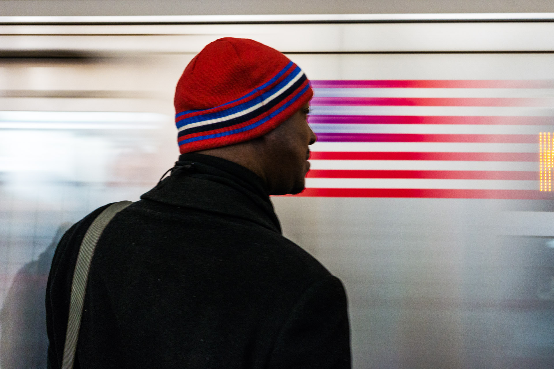 An American flag on a subway car is blurs as it speeds by a rider. Sony NEX-7 Sigma 30mm f/2.8 E ISO:400 1/20th f/4.0