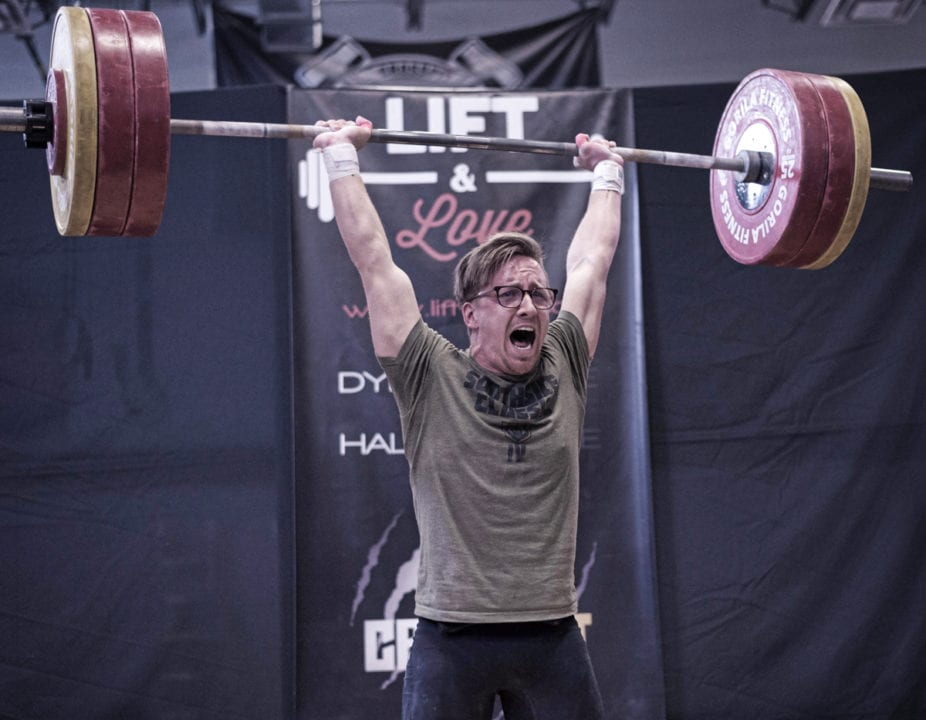 Olympic weightlifter successfully lifts a heavy Clean and Jerk