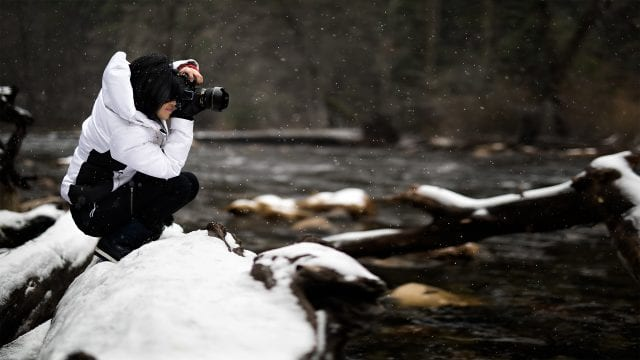 Female photographer takes picture without tripod