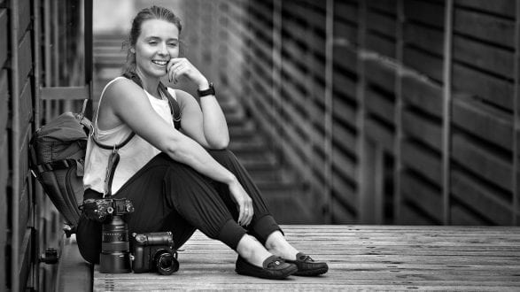 Female photographer with camera and prime lenses smiling