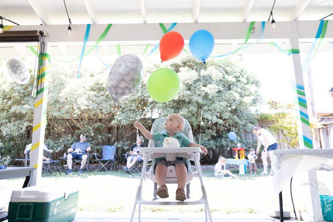Baby boy, birthday cake, and balloons